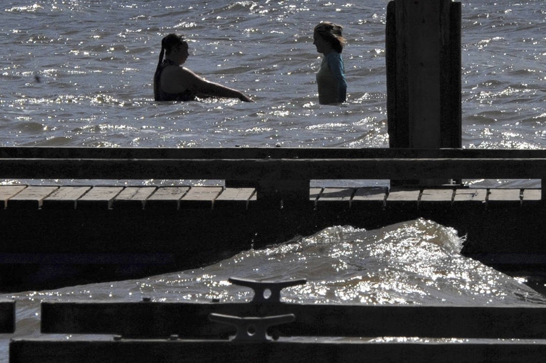 Swimmers are silhouetted against the morning sun while waves crash against the dock at the Lake Pleasant County Park. Strong northeasterly winds prevailed over the Labor Day Weekend. Photo by Lonnie Archibald