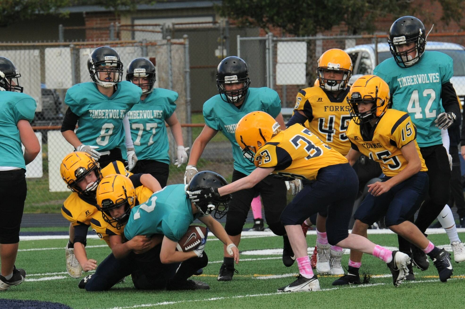 Above: Several Spartans converge on a Timberwolf running back. Photos by Lonnie Archibald