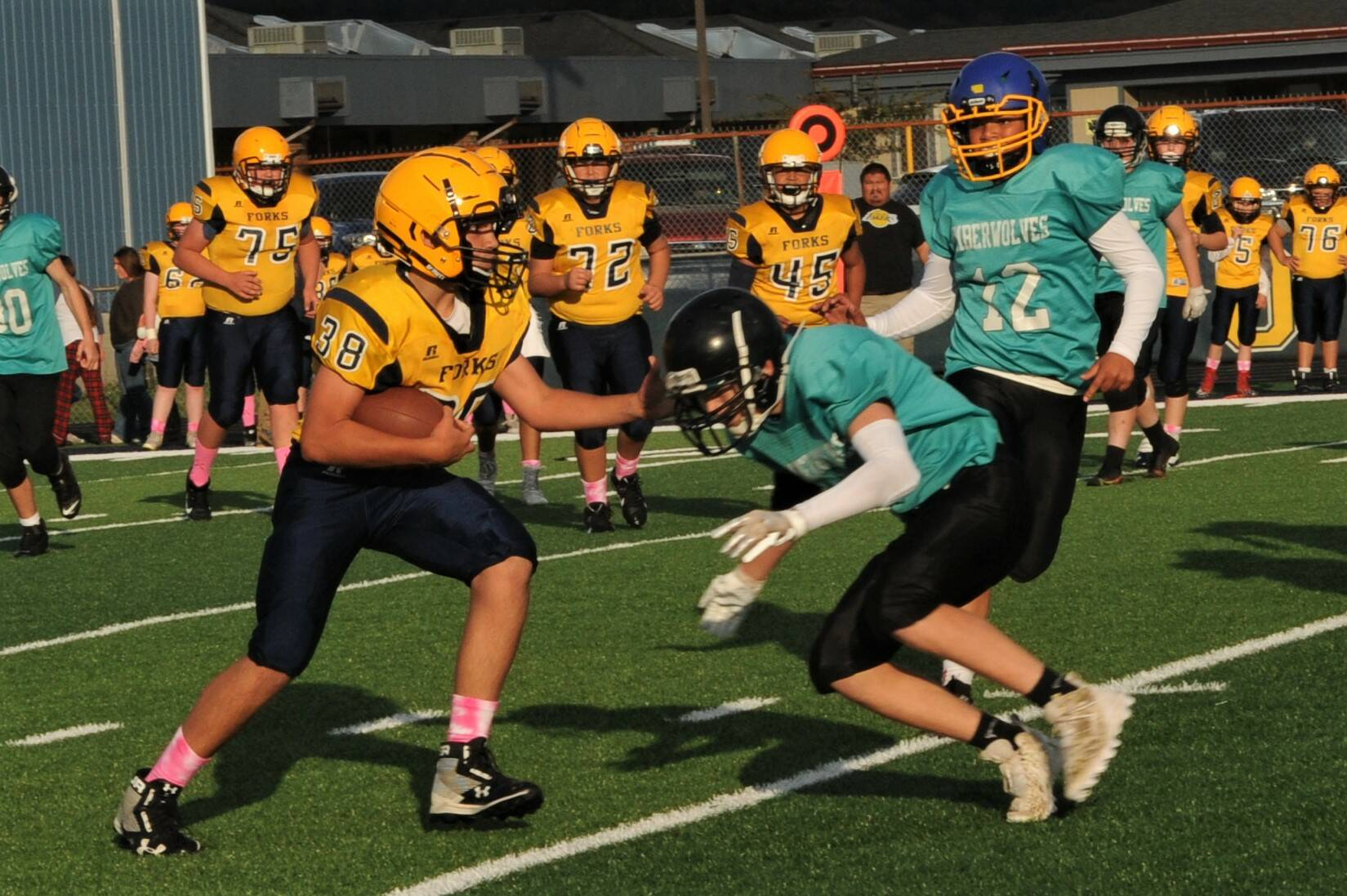 At right: Spartan Kade Highfield (38) carries the ball against Sequim defenders. Also in the action are Spartans Kenny Daman (75), Carter Coberley (72), and Carlos Soto (45).